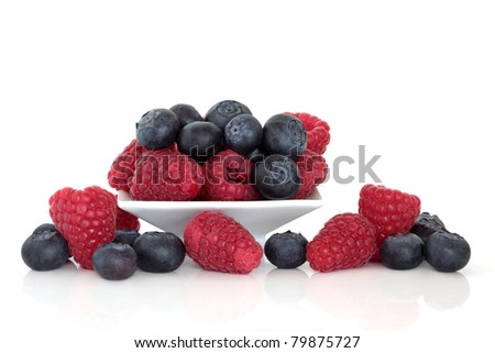 Blueberry and raspberry fruit in a porcelain dish isolated over white background.