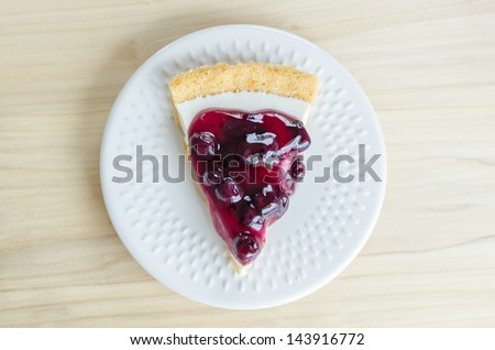 Blueberry cheese cake in white dish on the wood table - stock photo