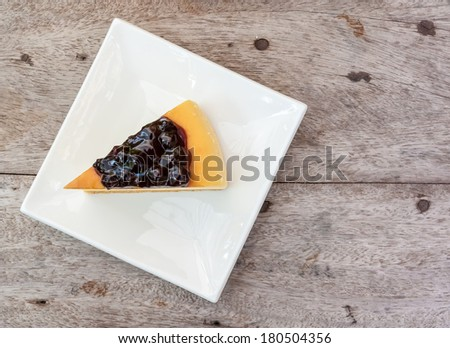 Blueberry cheese cake in white square dish on the wood table. - stock photo