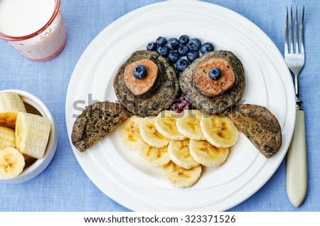 blueberry chocolate pancake with bananas in the shape of an owl for kids. toning. selective focus - stock photo