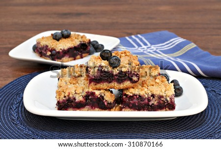 Blueberry cookie bars with a streusel topping, stacked on an oval plate. - stock photo