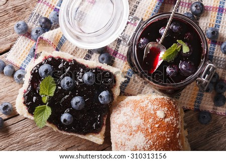 Blueberry jam and sweet bun close-up on the table. horizontal view from above - stock photo