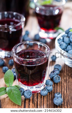 Blueberry Liqueur in a shot glass (on wooden background) - stock photo