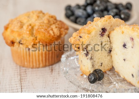 Blueberry muffin breakfast scene with bowl of blueberries in the background - stock photo