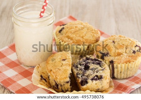 Blueberry muffin for breakfast with glass of milk and orange checkered napkin