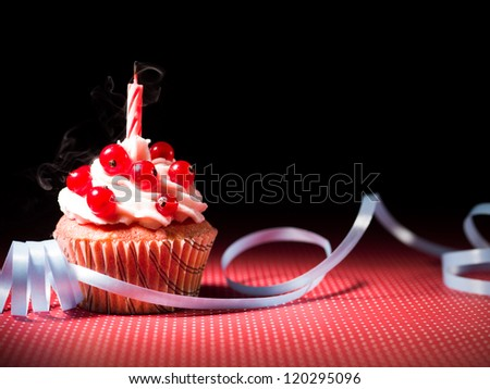 Blueberry muffin with  blown candle on the table Decorations with ribbons blue and dotted red and black background - stock photo
