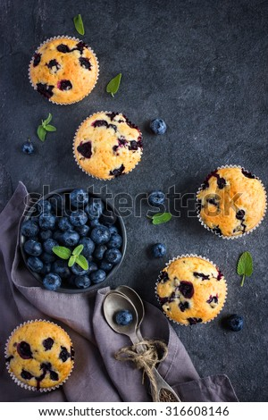 Blueberry muffins and fresh berries on dark background, top view - stock photo