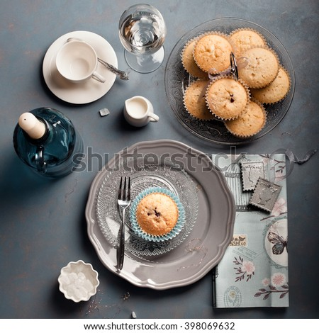 Blueberry muffins for tea/coffee time at a cafe or at home, on dark background, top view. Modern country style setting and accessories.