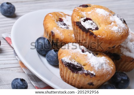 Blueberry muffins on a white plate closeup on a wooden table. horizontal