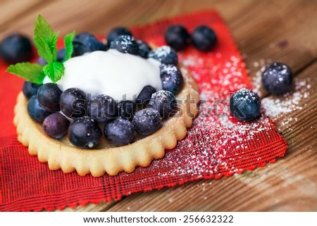 Blueberry  on a biscuit with creme on wooden background - stock photo