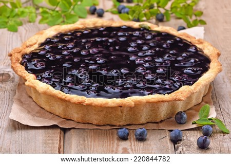 Blueberry pie and berries on rustic wooden table - stock photo