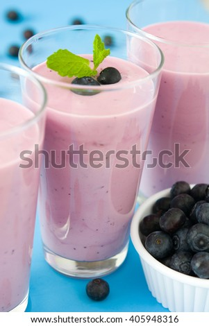Blueberry smoothie in a glass on a blue background