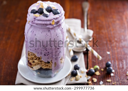 Blueberry smoothie with fruits and granola in jar - stock photo