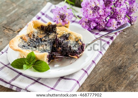 blueberry tartlet on a plate and purple flowers.