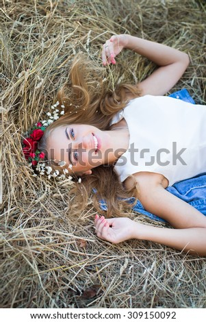 Blueeyed happy smiling teenage girl in wreath relaxing on hay  - stock photo