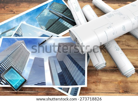blueprints and pictures of skyscrapers on wooden background - stock photo
