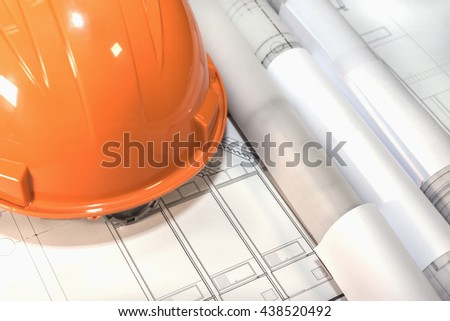 blueprints rolls and orange helmet over architectural plans project drawing, architect engineering and contractor concept - stock photo