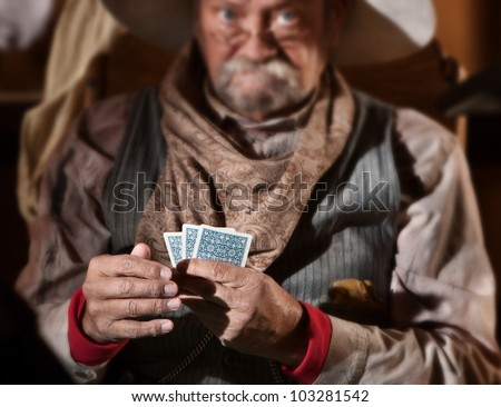 Bluffing card player in old American west saloon. Hands in focus. - stock photo