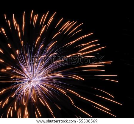 Bluish burst of fireworks inside reddish-yellow streaks from previous burst, off center - stock photo