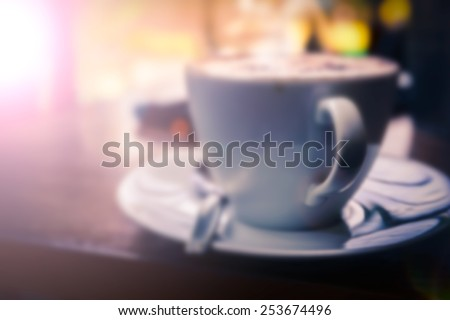 Blur a cup of Cappuccino with retro style coffee shop background memory under light classica tea in a glass of water background - stock photo