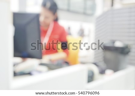 Blur abstract background air hostess ground staff working at check-in counter terminal.Blurry view receptionist work in front of computer for ticketing and loading baggage in international airport