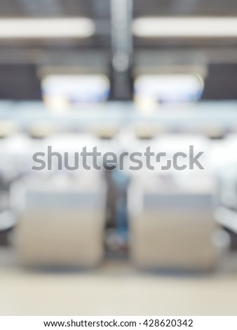 Blur abstract background bokeh of Terminal Departure Check-in at airport.Blurry view check in counter row with passengers travelling by plane at air port.Blurred image international airport interior - stock photo