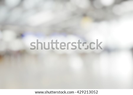 Blur abstract background bokeh of Terminal Departure Check-in at airport. Burry view of check in counter row with passengers travelling by plane at air port. - stock photo