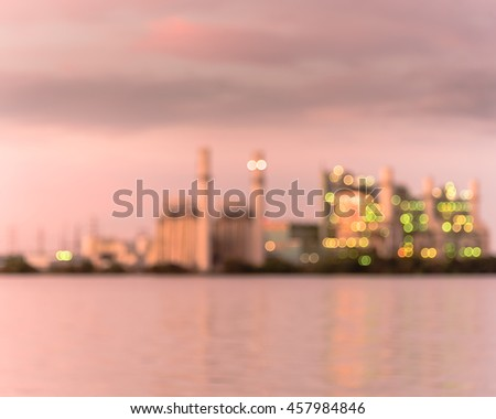 Blur abstract background of power plant at industrial park in San Antonio, US at twilight. The lake or reservoir in front provides cooling pond, recharged with treated wastewater for this power plant. - stock photo