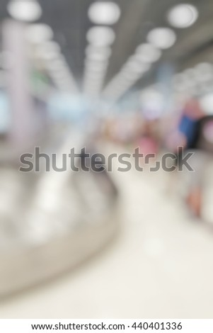 Blur abstract background of travellers waiting for luggage in baggage claim at international airport. Blurry view people wait at conveyer belt for suitcase. - stock photo