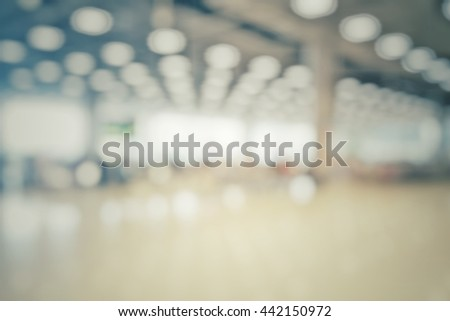 Blur abstract background of travellers waiting for luggage in baggage claim at international airport. Blurry view people wait at conveyer belt for suitcase in terminal hall vintage style bokeh effect. - stock photo