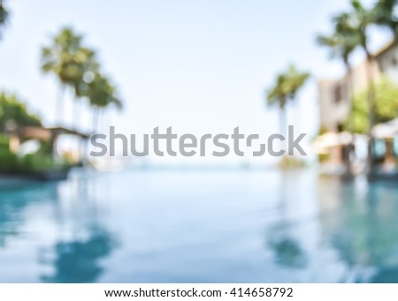 Blur abstract background resort hotel swimming pool with reflective water surface, blue cool clear sky, coconut palm tree row: Blurry perspective view of vacation summer holiday relaxation pond - stock photo