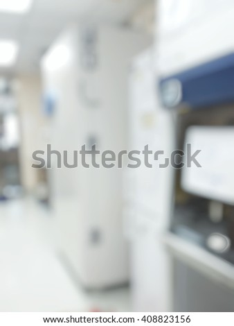 Blur abstract background white microbiology laboratory workstation office with cabinet and big freezer for research or education.Blurry view of empty modern white medical or chemical lab - stock photo