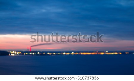 Blur background and bokeh of city lights. Bokeh of the city lights at twilight. The city with thermal power plant on the bank of Dnieper River at sunset.  Smoke dissipate across the sky.