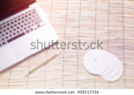 blur background, Blank compact disc with cover on laptop keyboar - stock photo