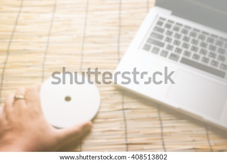 blur background, Business's hand holding Disk insert to laptop c