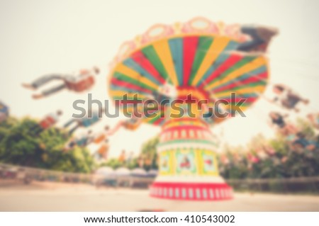 Blur background image of people enjoy roller swings in amusement park. - stock photo