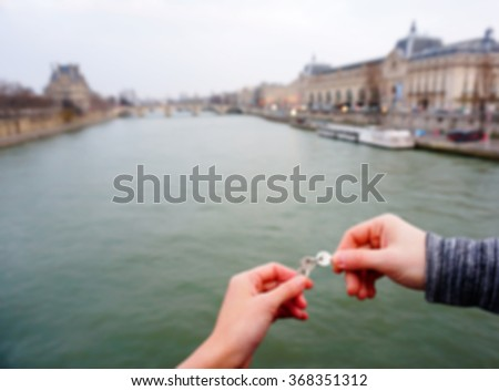 Blur background of couple's hands throwing love keys to the Seine river in Paris, France - stock photo