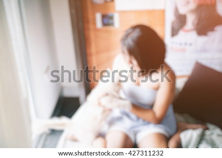Blur background. Young lonely woman in room