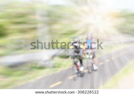 Blur bicycle riders in the park - stock photo