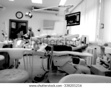 blur blurred dental clinic section in hospital with patient on tactical chair waiting for nurse and dentist in teeth operation black and white version - stock photo