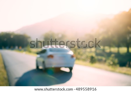 Blur car on country road with sun light abstract background. Copy space of transportation and travel concept. Retro tone filter color style.