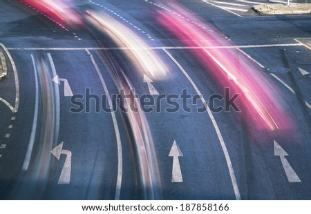 Blur cars in rush hour on white markings and arrows. - stock photo