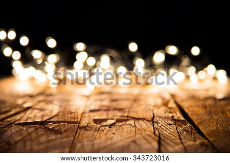 Blur christmas lights on wooden planks, low depth of focus with copyspace - stock photo