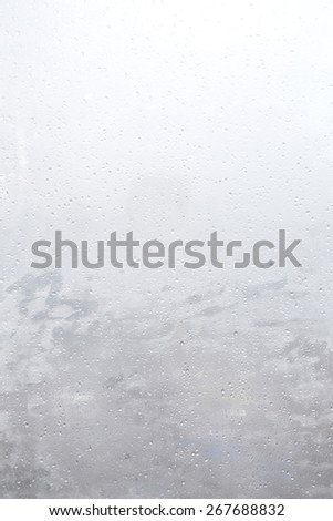 Blur City behind Building Glass Window with Rain Water Drops - stock photo