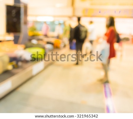 Blur female passenger waiting for luggage on conveyor belt in terminal of airport when arrival - stock photo