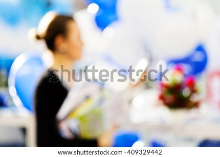 Blur image of a woman with balloons at technology expo; blurred 100%