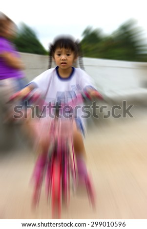 Blur image of children learn to ride a bike with fear. - stock photo
