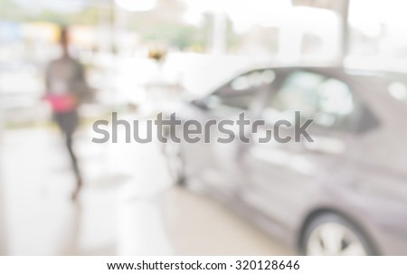 blur image of Commercially cars stand in show room of car shop. - stock photo