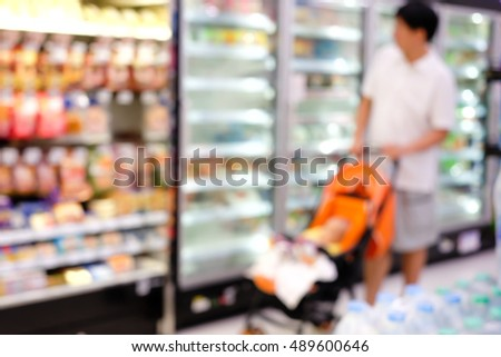 Blur image of dad and son go shopping at supermarket - for background