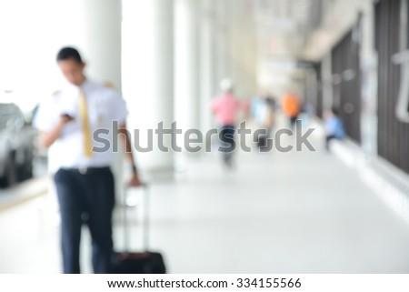 Blur image of flight crew and people walking in airport corridor - stock photo